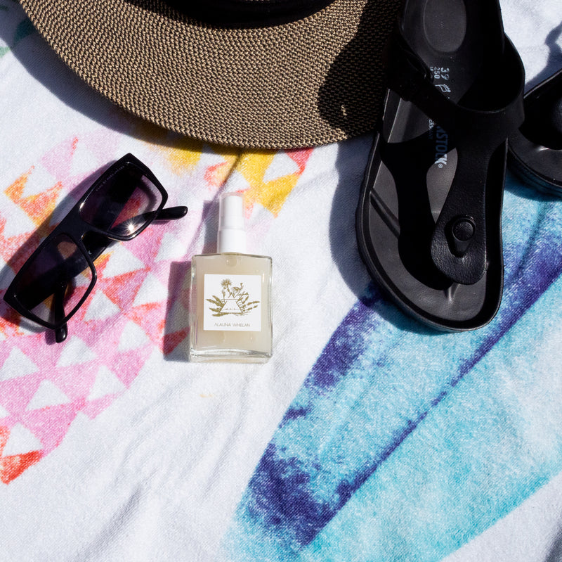 air ritual mist on beach towel with sun hat sunglasses and sandals