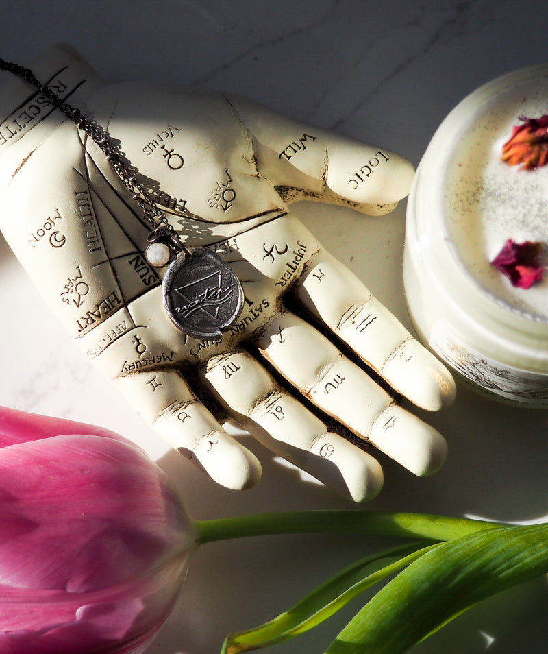 plaster hand holding silver water sign medallion necklace amongst rose petal topped candle and fresh tulips
