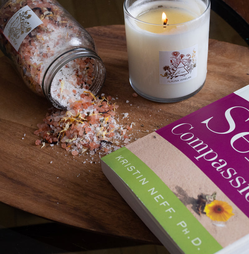 Alauna Whelan fire candle, bath soak, and book on wooden tray