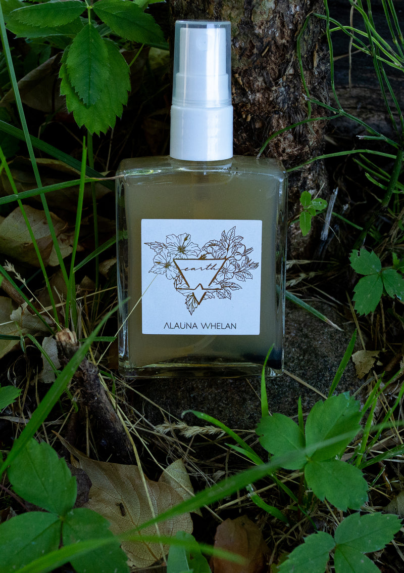 crystal infused ritual mist with white and gold label on forest floor