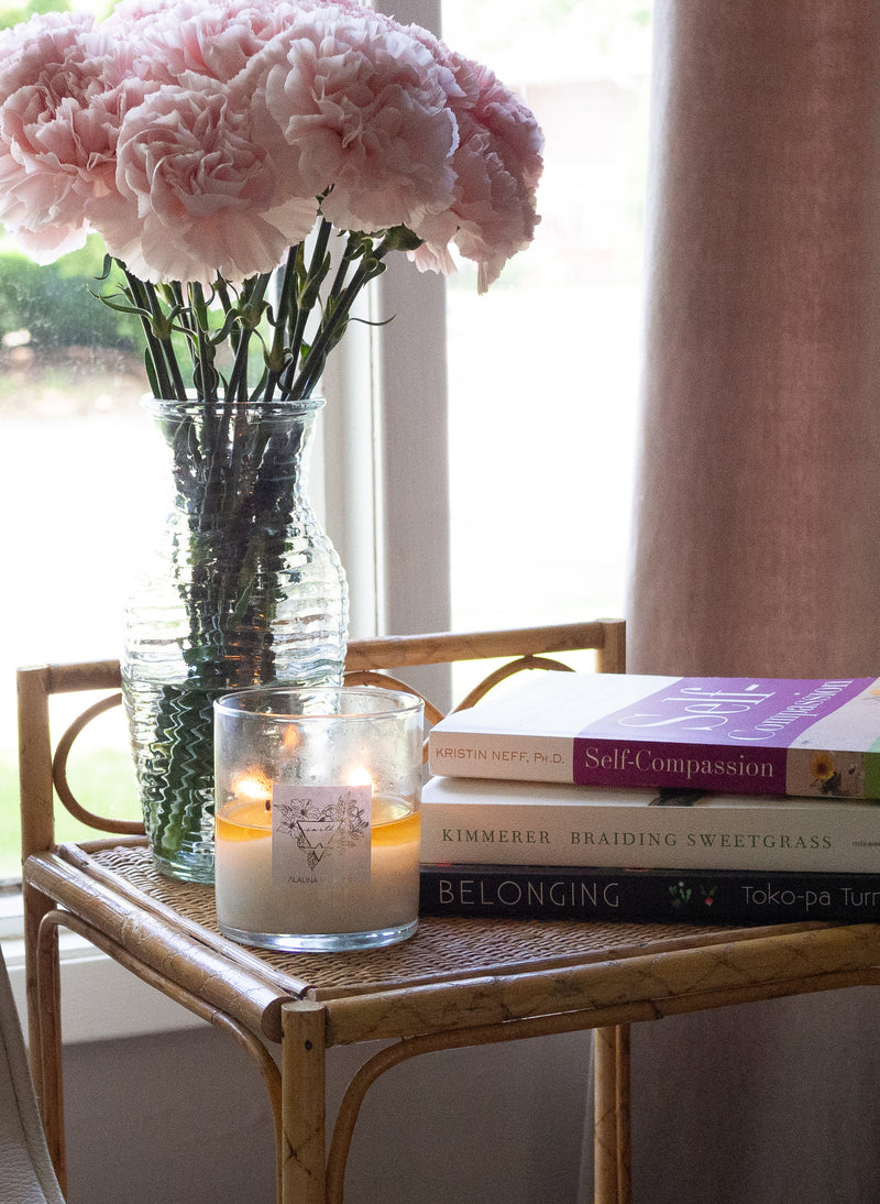 earth sign candle on wicker table in front of a window with carnations and self help books