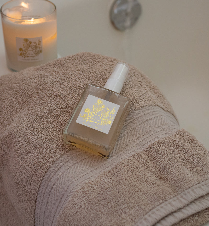 fire ritual mist and botanical soy candle on fluffy towel at edge of bath tub