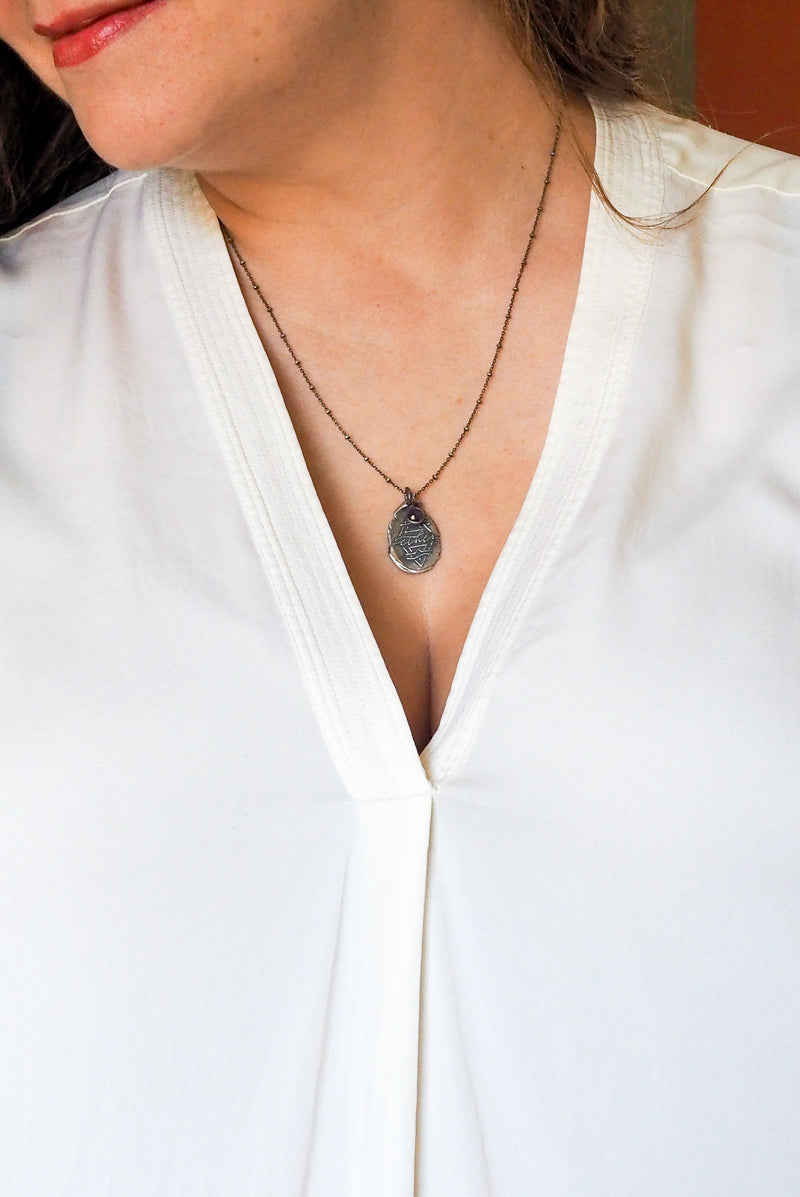 silver medallion necklace with alchemical symbol on woman in white top