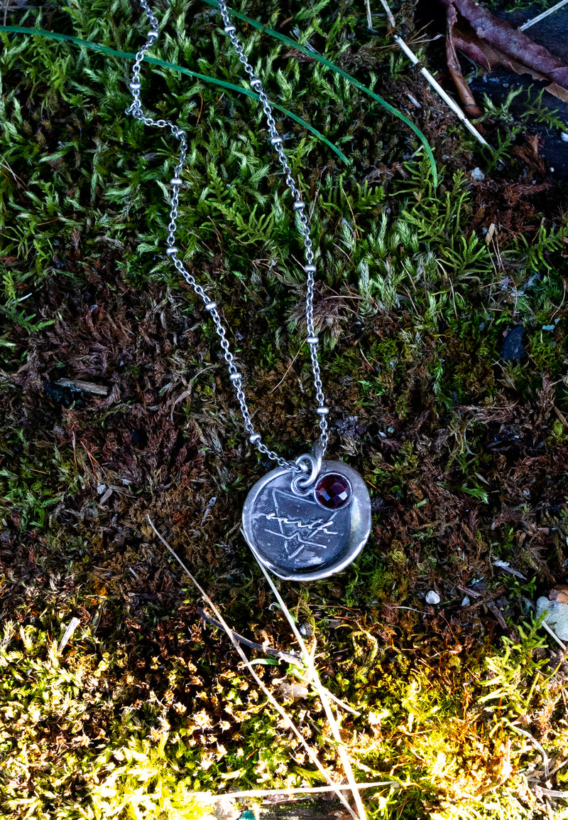 silver earth sign talisman necklace on mossy background
