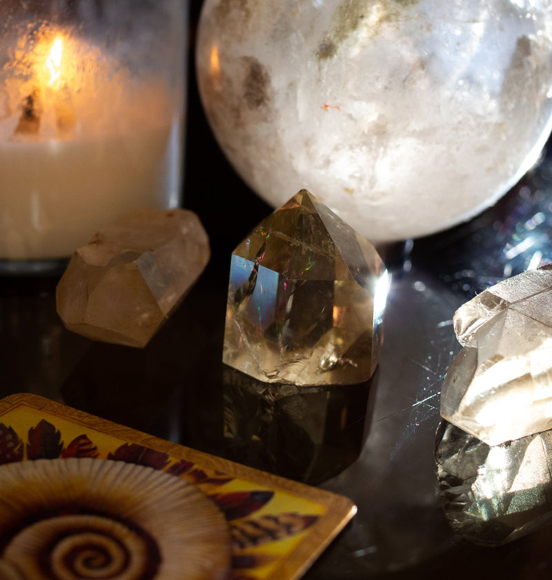 yellow and clear quartz crystals with candle and sunbeams
