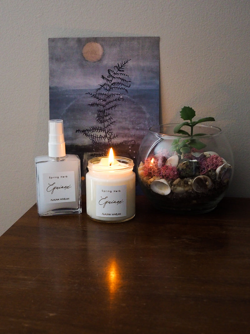 candle and ritual mist on wooden table with small plant and moon art