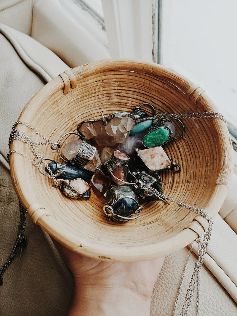 crystal talisman necklaces in small wicker bowl