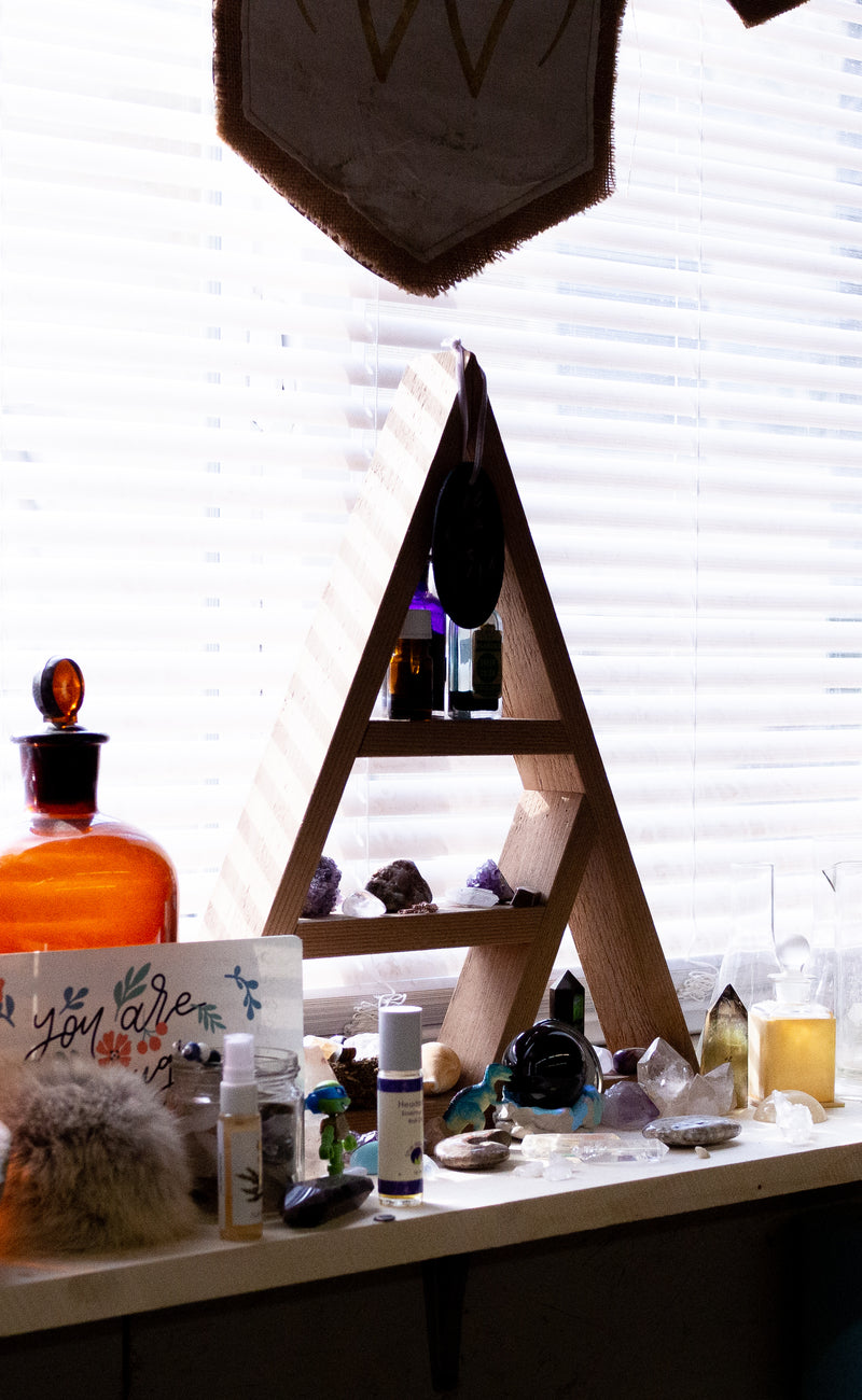 window with apothecary shelf, raw crystals, bottles, perfumes and mists