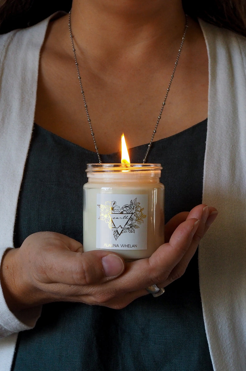 womans hand holding lit botanical candle