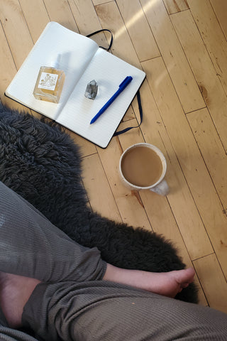 Morning meditation with crystals, coffee, and journal. Woman in soft clothes sitting on sheepskin