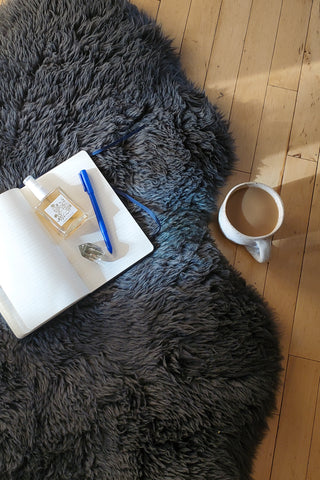 Meditation mist, journal and crystal on sheepskin rug with cup of coffee nearby