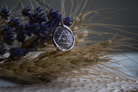 silver medallion layering necklace with air alchemical symbol with wheat and lavender background