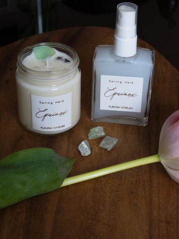 spring equinox candle and ritual mist with green crystals and tulips on wooden tray