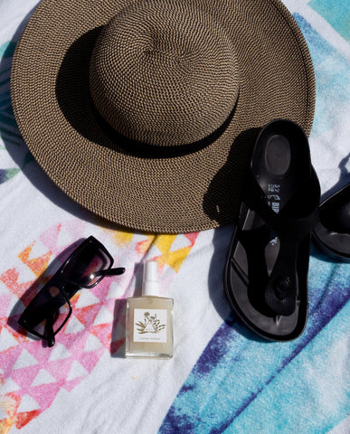 ritual mist with sun hat sunglasses birkenstocks on beach towel