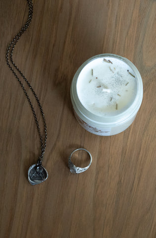 botanical luxury candle with silver talisman necklace and ring on wooden tray
