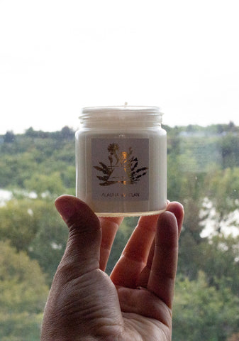 air sign candle in hand with green trees in background