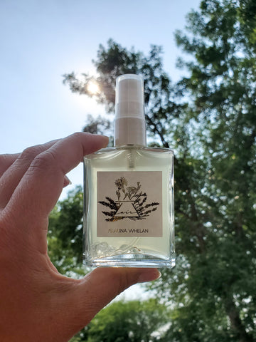 air sign crystal infused mist in palm of hand with trees and sun in the background
