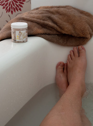 woman's legs in a bath tub with bath salts and towel