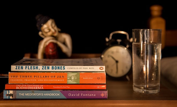 nightstand with books, buddha, and water glass