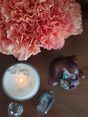 birds eye view of luxury candle with fresh pink carnations and crystals