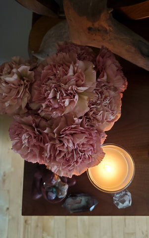 birds eye view of soy intention candle with crystals and pink carnations