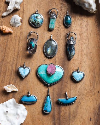 collection of blue green and teal crystal talisman jewelry and altar art pieces