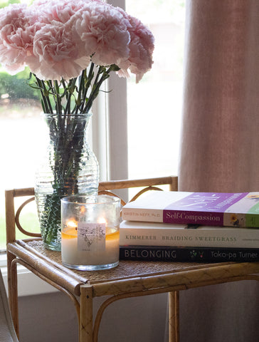 pink carnations, books, and intention candle
