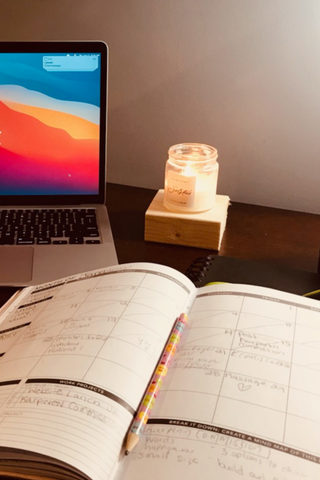 desk with solstice candle, laptop, and journal