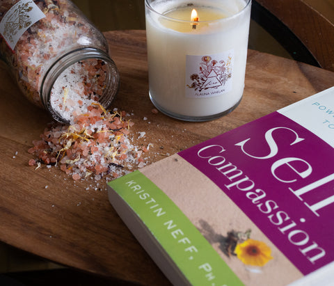 candle bath soak and book on wooden tray