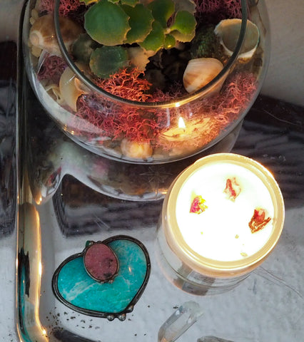 birds eye view of blue and pink crystal altar art with lit soy candle and succulent bowl on mirrored tray