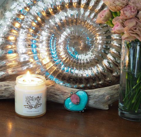 green and pink crystal altar art piece with mirrored silver shell soy candle and fresh cut flowers
