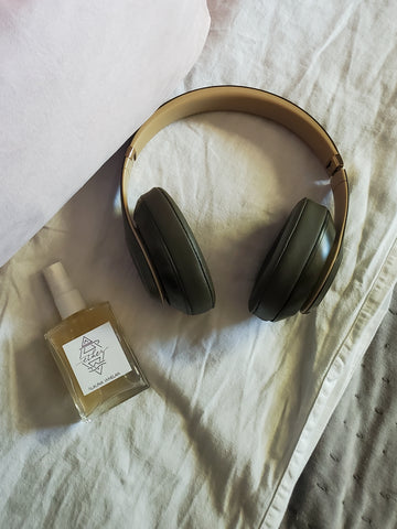 luxury crystal infused ritual mist on white bedding with beats headphones