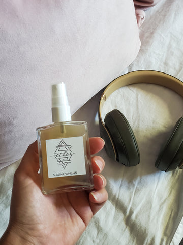 hand holding luxury crystal infused linen spray with white sheets and headphones in the background