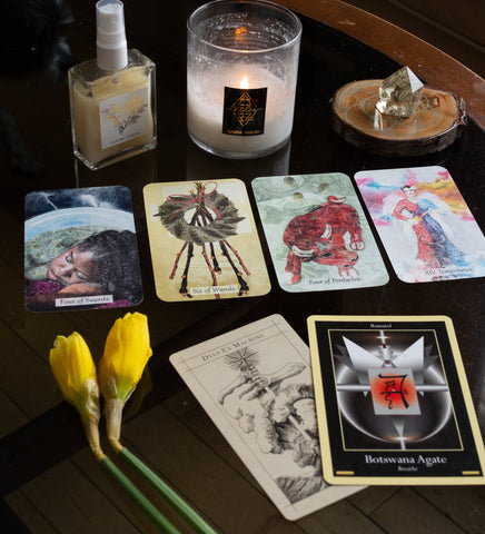 ritual mist and candle with tarot cards and crystals
