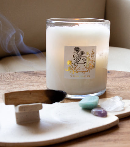fire sign element candle on wooden tray with palo santo, smoke tendrils, and small crystals