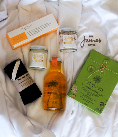 a variety of self-care spa products on plush white bath robe