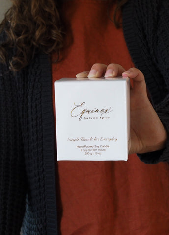 woman holding luxury soy autumn equinox spice boxed candle