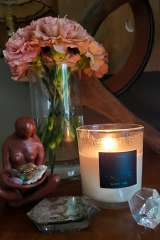 luxury new moon soy candle with crystals goddess statue and fresh cut flowers