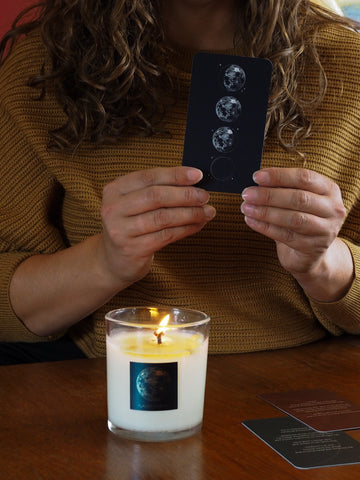 woman in yellow knit top holding lunar oracle cards with lit full moon luxury soy candle burning