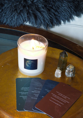 full moon luxury soy candle with oracle cards and crystals arranged on gold tray
