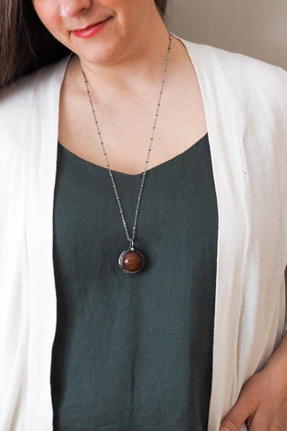 rustic chunky red crystal sphere layering talisman necklace on woman in blue top