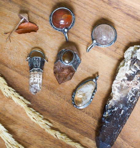 collection of red and orange rustic crystal talismans on wooden background