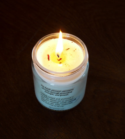 lit soy intention candle on dark background