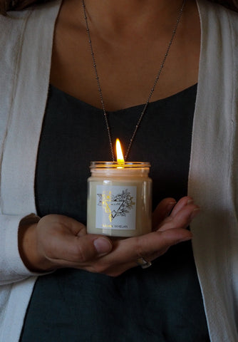 womans hand holding earth sign intention element candle