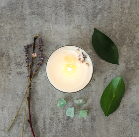 top view of soy candle with leaves crystals and herbs