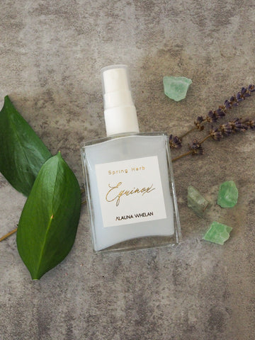 spring equinox aromatic ritual mist with crystals leaves and branches in background