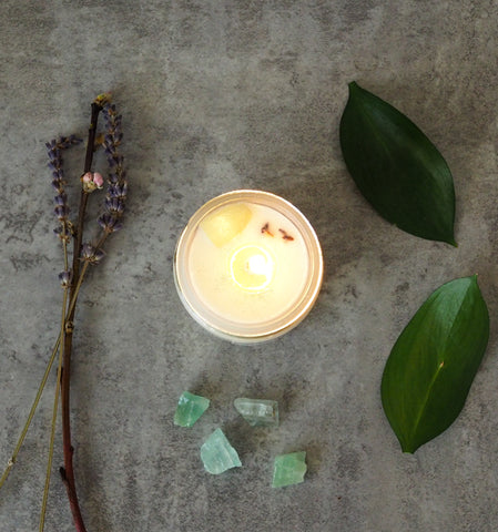 birds eye view of spring soy crystal infused candle on grey background with some leaves and branches