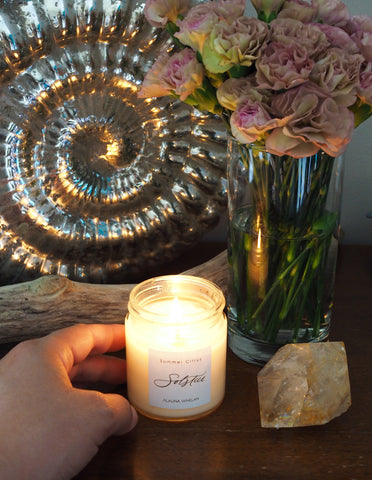 hand holding summer soy candle with fresh blush toned carnations and large raw crystal
