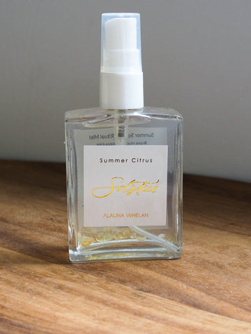 crystal infused body mist with gold foil and white label on wooden tray with white background