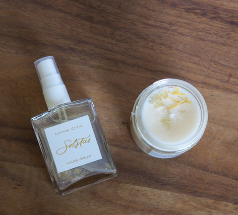 summer solstice soy candle and room mist with white and gold labels on wooden tray